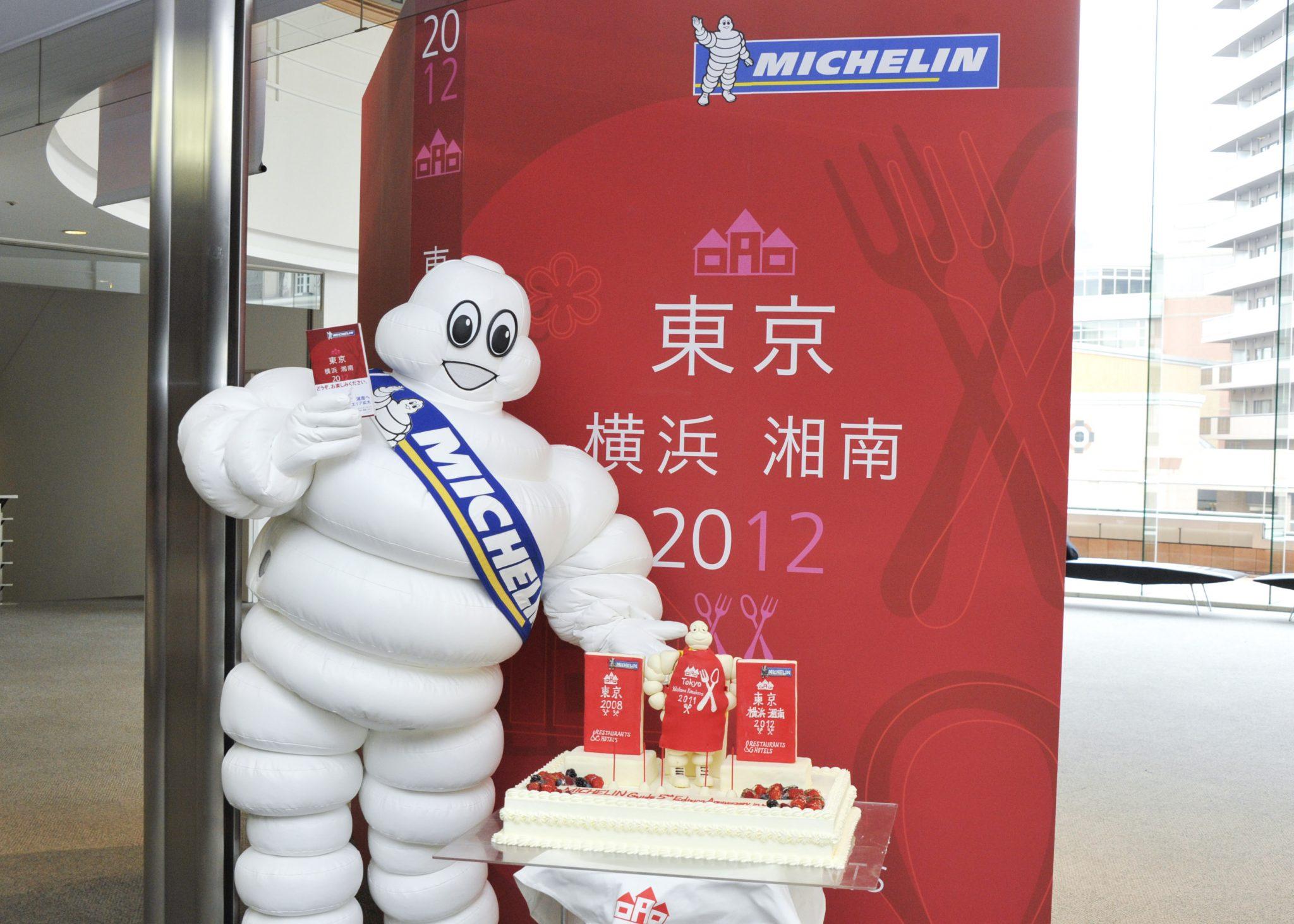 ミシュランマンと発行5年目記念ケーキ(展示パネル前2)